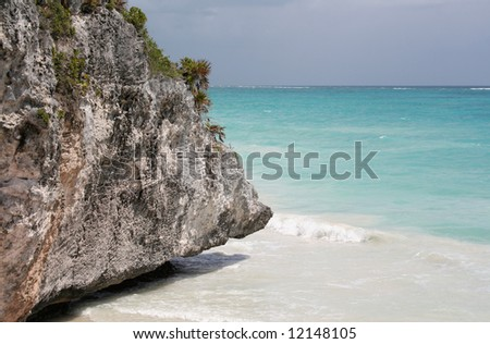 The rocky beach jagged, but beautiful turquoise sea of Tulum in Mexico. - stock photo