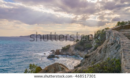 The rocky coast of the sea, the city and the sky
