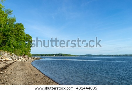 The rocky coastline and rippling water at Northport, Maine in the late springtime. - stock photo