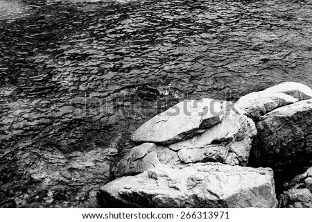 The rocky coastline. Rock in the sea. Black and white - stock photo