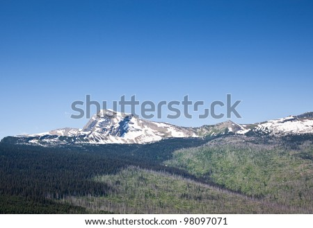 The rocky mountain of Heavens Peak still covered with snow on a bright summer day.  The foot hills below the peak show evidence of a previous wildfire leaving dead standing timber. - stock photo
