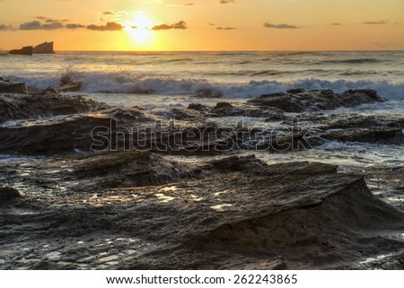 The rocky shore of Playa Pelada looks like waves of rock, with the surf crashing at Sunset on the Pacific coast of Costa Rica. - stock photo