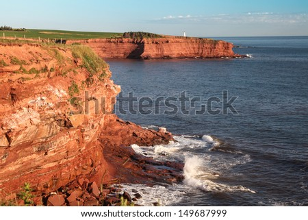 The rocky shore of Prince Edward Island at daybreak illuminating the cliffs and rocks bright red. - stock photo