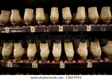The roller skates are all lined up ready to be worn at the roller rink. - stock photo