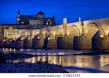 The Roman Bridge (Puente Romano) over Guadalquivir river and Mosque Cathedral (Mezquita) at dawn in Cordoba, Andalusia, Spain. - stock photo