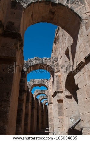 The Roman Colosseum in El Djem is one of the largest Colosseums. Residuel archs against the blue sky background are eye-catching. - stock photo