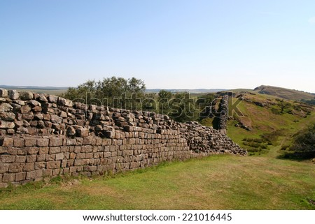 The Roman remains of the historic Hadrian's  Wall meandering over the Walltown Craggs in Northumberland, England. - stock photo
