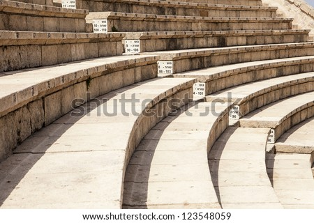 The Roman theater at Caesaria in Israel has been restored and is now used for modern performances. The tiered rows of seating provide a clean, repetitive pattern that arcs into the distance. - stock photo