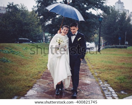 The romantic walking of newlyweds. The groom and bride are walking under umbrella in the rain in the park. They are happy. Newlyweds in love. Tis is their wedding day.  - stock photo