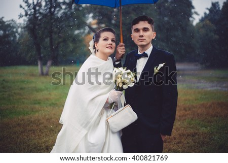 The romantic walking of newlyweds. The groom and bride are walking under umbrella in the rain in the park. Newlyweds in love. Tis is their wedding day. They became husband and wife this day. - stock photo