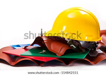 The roof is made from durable plastic in different colors and shapes, a yellow hard hat, screws on a white background - stock photo
