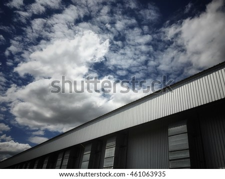 The roof of big warehouse on blue sky and clouds background