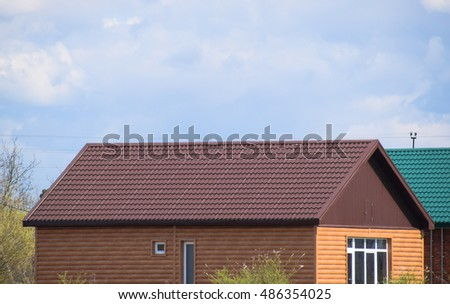 The roof of corrugated sheet on the houses. Individual homes with roof made of profiled sheet metal.