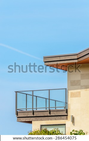 The roof of the house with balcony over blue sky.