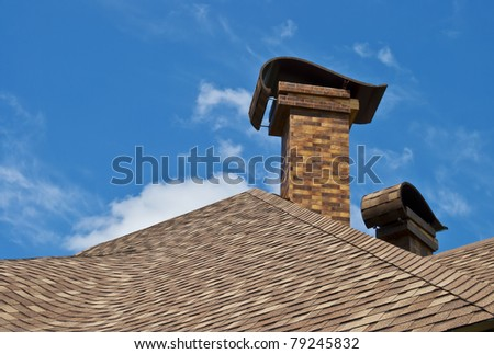 The roof of the house with two chimneys in the new design against the blue sky with clouds. - stock photo