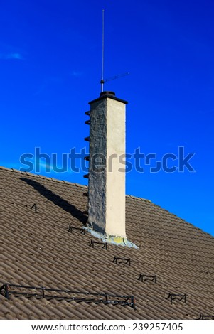 The roofing tiles house roof with chimney and safety metal ladder to climb sky background - stock photo