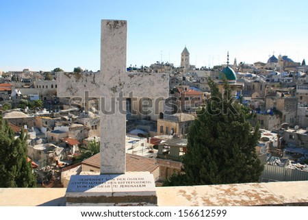 The roofs of the old city of Jerusalem with a cross in the foreground, Israel.