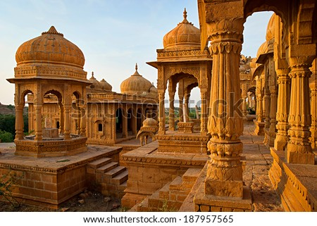 The royal cenotaphs of historic rulers, also known as Jaisalmer Chhatris, made of yellow sandstone at sunset. Bada Bagh in Jaisalmer, Rajasthan, India - stock photo