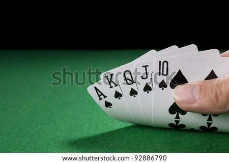 The Royal Flush on a green poker table against black. - stock photo