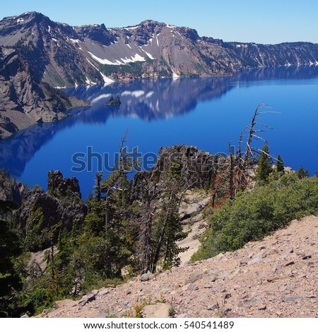 The rugged crater with Phantom Ship and reflections at Crater Lake on a sunny afternoon.