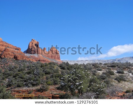 The rugged landscape around scenic Sedona, Arizona, offers lush trees and brush and dramatic mesas, cliffs and monuments.  Here the red rock hills and vegetation are frosted with snow. - stock photo