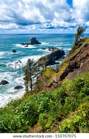 The rugged Oregon coastline in the Northwest United States features green cliffs, sea stack rocks and dramatic clouds overhead - stock photo