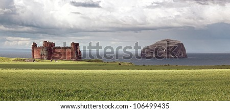 The ruin of Tantallen Castle and the Bass rock island off the shore of North Berwick in Scotland - stock photo