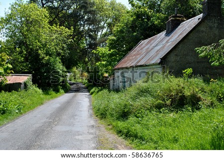 the ruins of a traditional irish cottage on a small laneway - stock photo