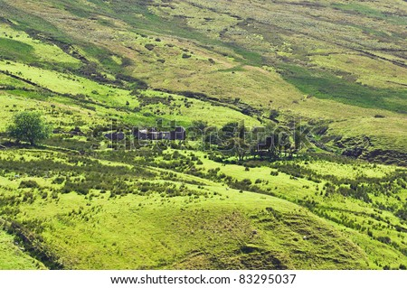 The ruins of an old stone cottage, once a family home, lie abandoned beside a winding river in the Sperrin Mountains, Londonderry, Northern Ireland, a historical relic from times of poverty or famine. - stock photo