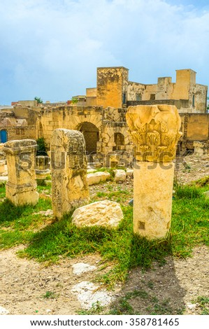 The ruins of the ancient columns decorated with carvings in archaeological site of the Roman baths, El Kef, Tunisia. - stock photo