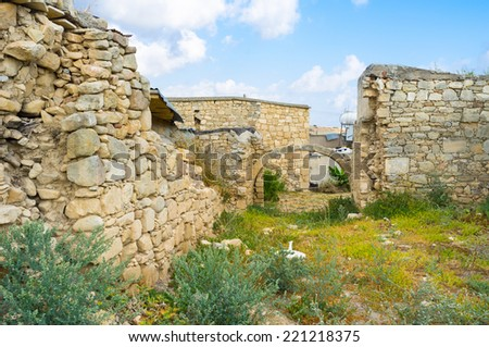 The ruins of the old residential house with preserved stone wall and the arch at the entrance, Kouklia, Cyprus. - stock photo