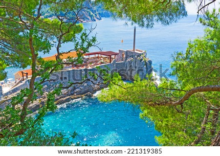 The ruins of the Petrovac fortress nowadays serve as the restaurant with large terrace and the viewpoint, that overlooks the coast, harbor and old town, Montenegro. - stock photo