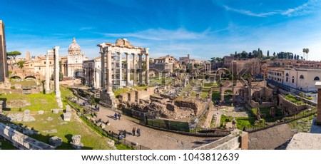 The ruins of the Roman Forum in Rome, Italy with the Colosseum visible in the back