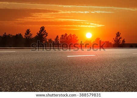 The rural asphalt road in the sunset - stock photo
