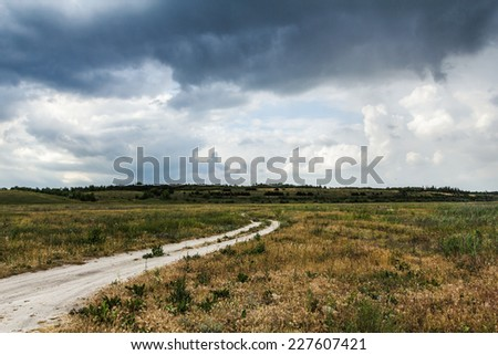 The rural dirt road, beautiful countryside in cloudy weather - stock photo