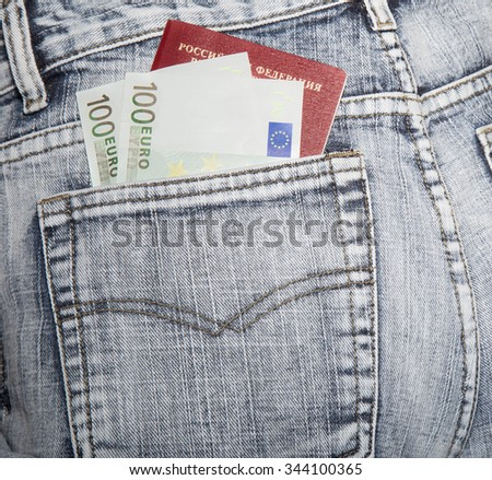 The Russian passport and two notes on hundred euros in a hip-pocket of jeans - stock photo