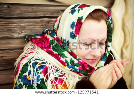 The Russian woman in a shawl warms hands near an izba - stock photo