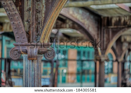 The rusting and corroded girders with amazing architectural details holding up the ceiling of an abandoned train station - stock photo