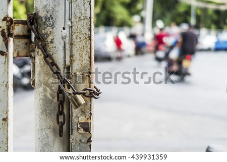The rusty chain and lock on the park gate post - stock photo