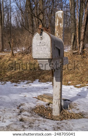 The rusty metal mailbox on the rural country road. - stock photo