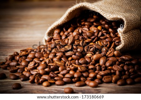 The sack of coffee beans on wooden background - stock photo