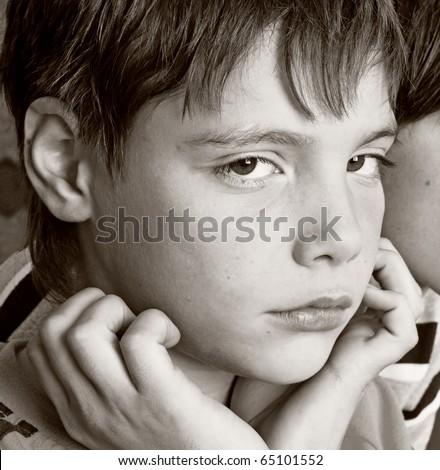 The sad boy looks having leant against hands - stock photo