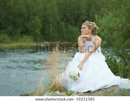 The sad bride sits on river bank and looks afar - stock photo