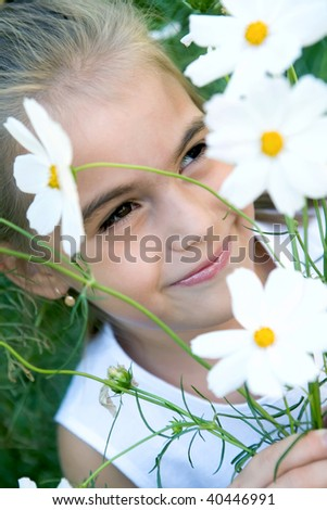 The sad girl and wild flowers. Small depth of focus - stock photo