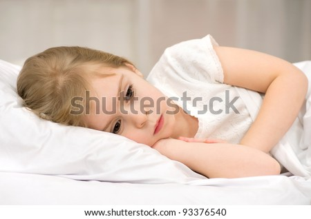 The sad little girl lying in bed - stock photo