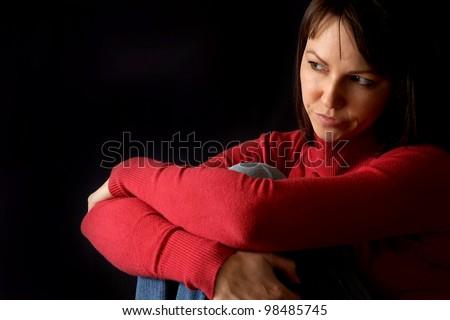 The sad woman sitting on a dark background - stock photo
