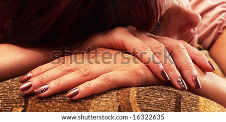 The sad woman who has lowered a head on hands,focus on a hand