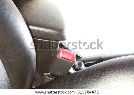 The safety belt equipment at the black color car seat represent the car safety part concept related idea.  - stock photo
