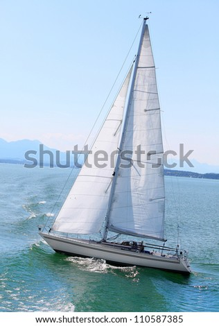 The sail boat in early morning on the mountain lake. Chiemsee is a biggest freshwater lake in Bavaria, Germany. - stock photo