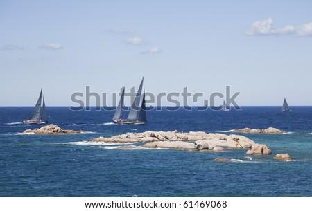 The sailboat racing around the island in Sardinia. - stock photo